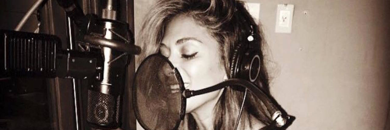 A photo of Nicole singing into a mic, recording a song.