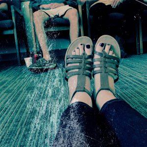 woman's outstretched feet on floor of waiting room or group therapy with others facing her
