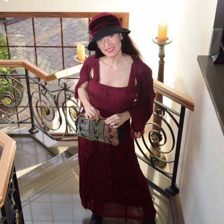 woman dressed up in a hat and dress holding a purse