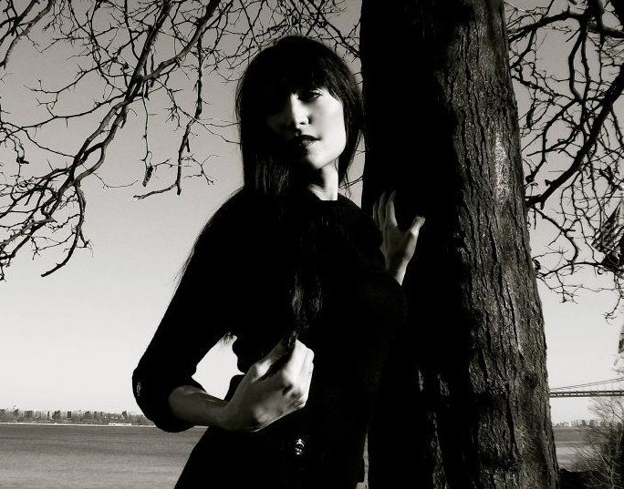 black and white photo of woman standing outdoors by a tree