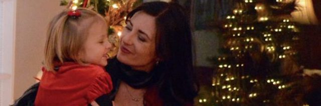 A woman holding her daughter in front of the Christmas tree