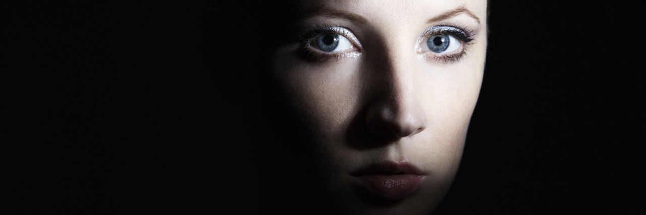A woman with a dark shadow covering some of her face.