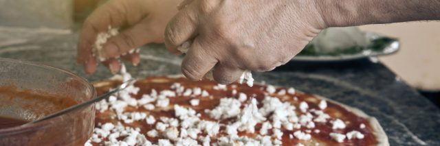 close up of man making pizza putting cheese on base