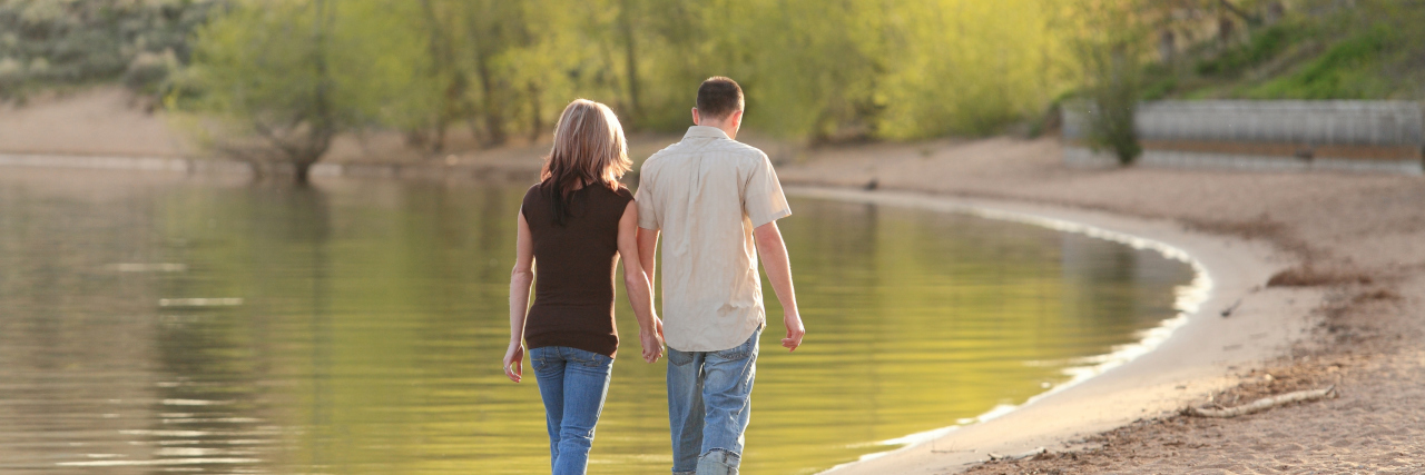 Couple walking together on a lake beach and holding hands.
