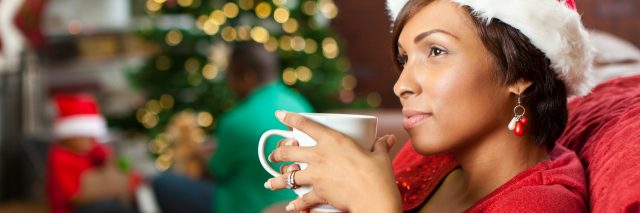 woman drinking from a mug next to the christmas tree