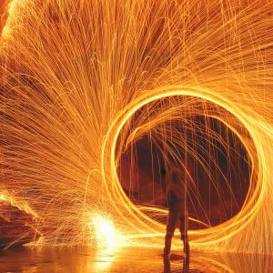 Woman standing in front of a ring of fire.