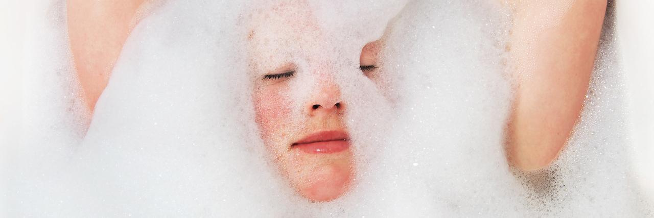 young woman taking a foam bath.