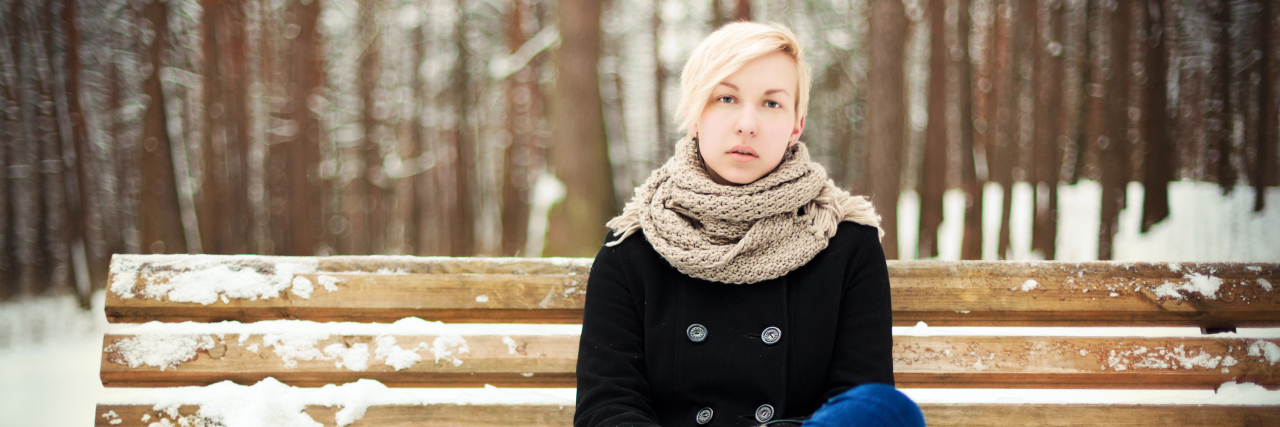 Young blonde woman sitting on a bench in winter park