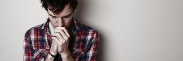 worried young man against plain wall looking down with hands closed
