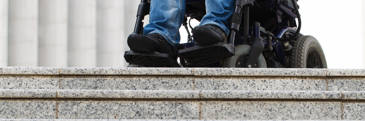 Wheelchair user in front of staircase barrier.