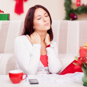 woman in pain on her couch surrounded by christmas presents