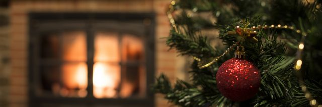Close-up of ornaments on the Christmas tree near a fireplace