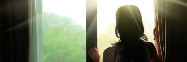 woman opening the curtain to look at the sunrise