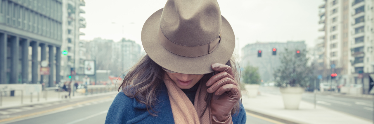 eautiful young brunette with hat posing in the city streets