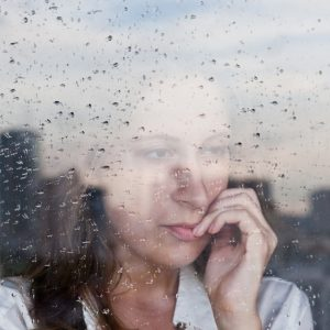 young woman looking anxious out of rainy window