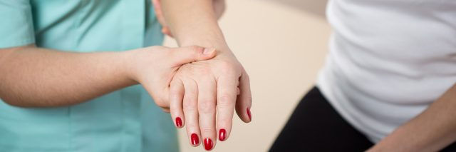 A close-up image of a physical therapist helping a patient, holding her arm and hand.