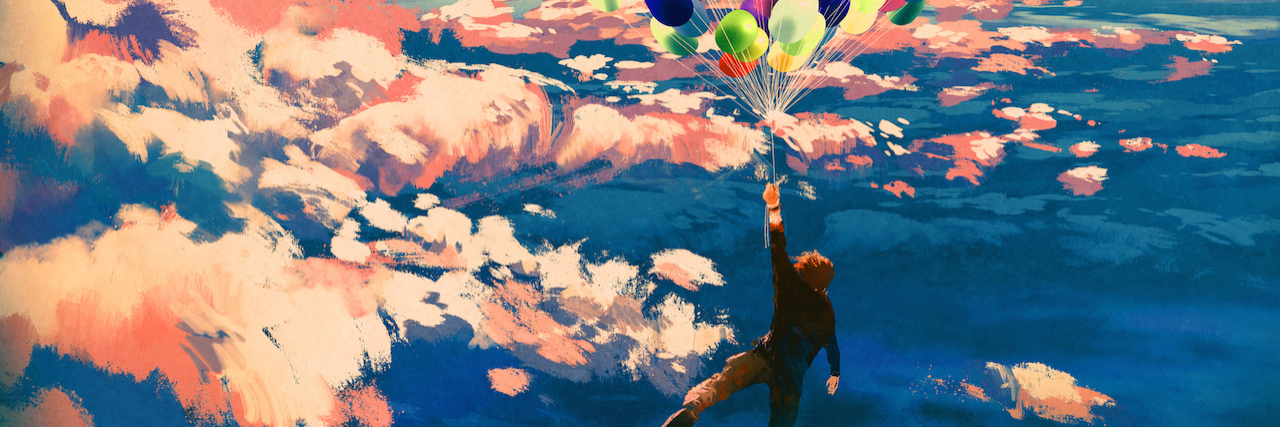 A man with a bunch of balloons floating in the air