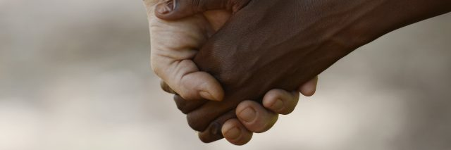 African Peace Symbol. White woman holds hands with a little native African girl, in Bamako, Mali. A black child and a white woman hold hands. Peace on earth symbol. Took this pic during my stay in Bamako, Mali in September 2015. A beautiful shot with lots of possible background symbols. No to Racism!