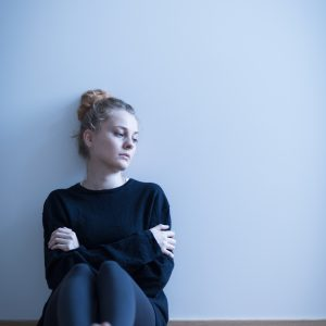Photo of a depressed girl sitting with crossed arms
