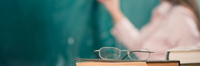 glasses and books on teacher's table in focus with female teacher at background at chalk board
