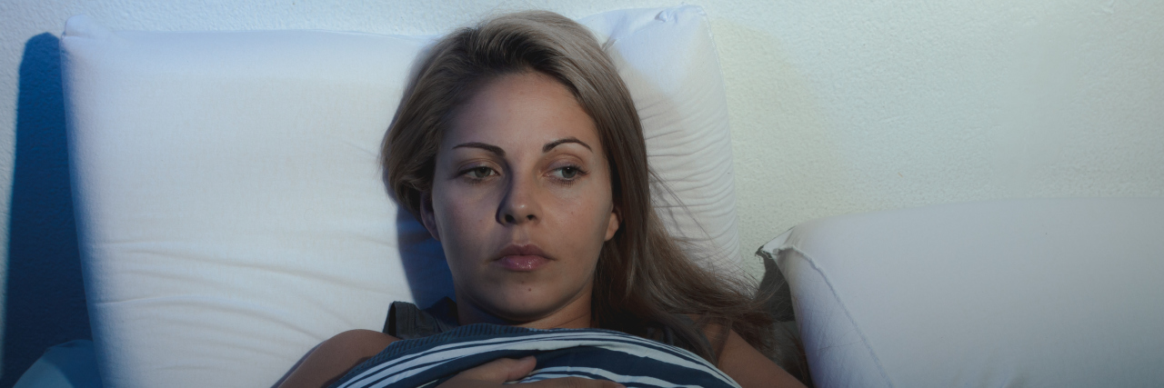 young blonde woman lying on the bed awake