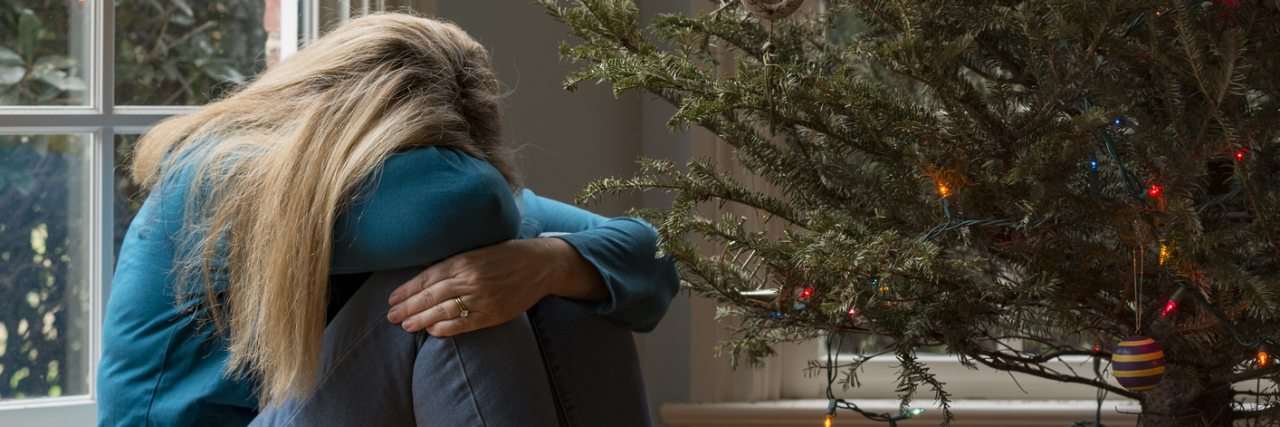woman beside dying christmas tree crouched on floor hugging knees depression