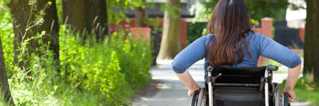 Young woman in wheelchair rolling in the park.