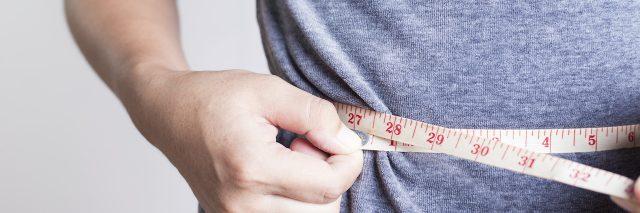 Person measuring their waistline