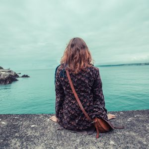 young woman sitting at water's edge by harbour isolated