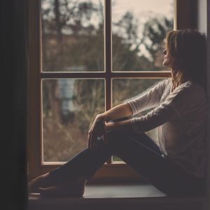 A woman siting on a window sill, looking outside.