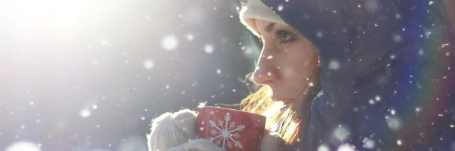 woman drinking from a red mug outside in the snow