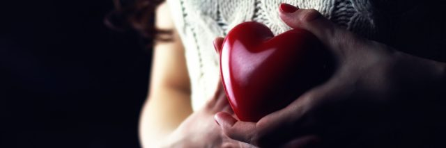 woman with heart in hands resting on chest
