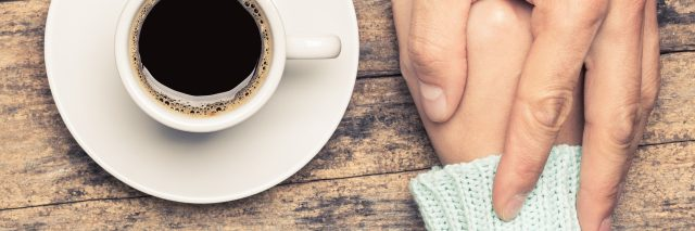 close up of people holding hands on table beside cup of coffee
