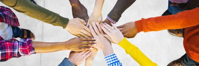 Group of Diverse Multiethnic People putting hands together to indicate Teamwork