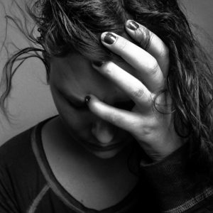 black and white portrait of emotional woman holding head looking down with messy hair at home, stress, depressed, sad, somber