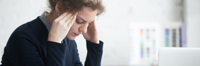 young woman in front of laptop stressed depressed hands at temples