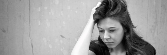 A black and white image of an upset woman sitting on the ground.
