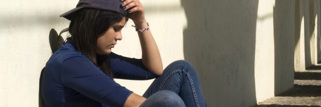 woman sitting against wall sad depression
