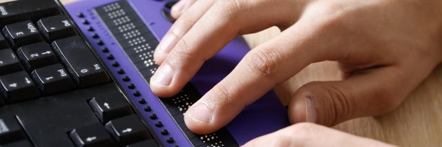 Blind person using computer with braille display.