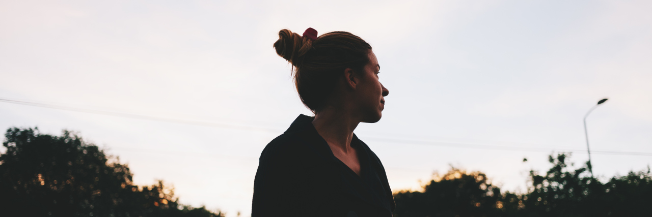 The silhouette of a young woman looking at sunset in the distance