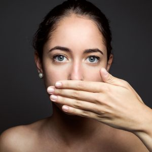 young woman covering her mouth with hand. Isolated.