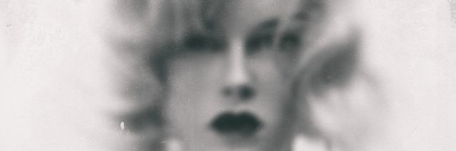 A black and white vintage image of a woman, slightly blurred.