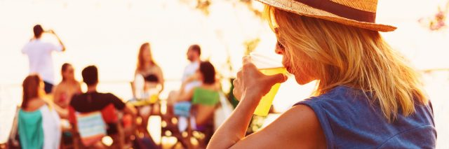 young woman alone at beach party drinking beer