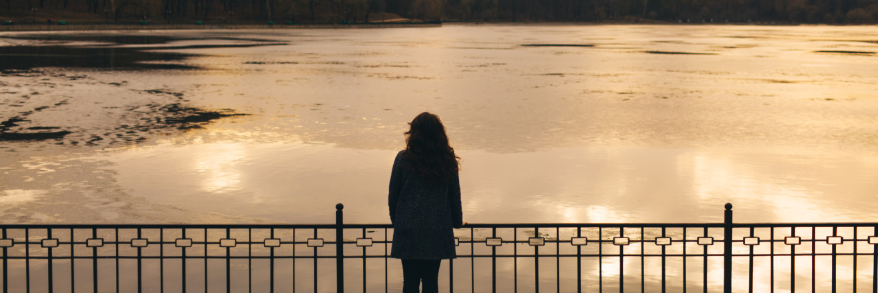Lonely woman alone in winter at sunset