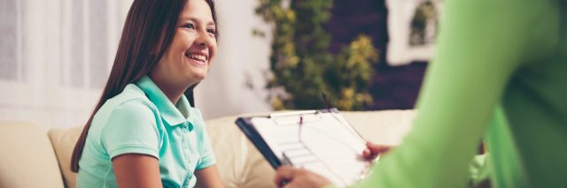 Girl teenager is happy after a successful therapy by psychologist counselor