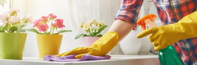 woman cleaning surface wearing yellow rubber gloves