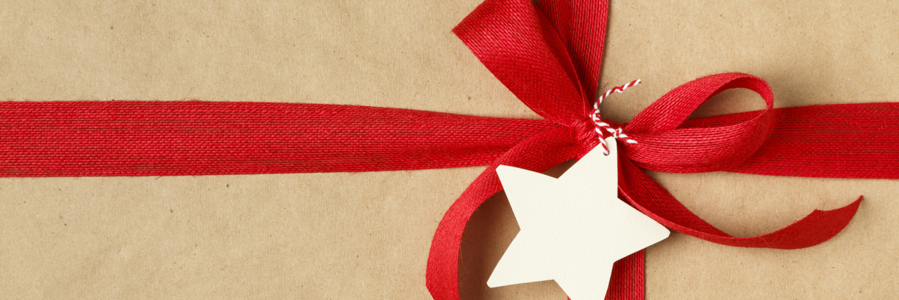 A close-up of a Christmas gift with a red ribbon and bow on top.