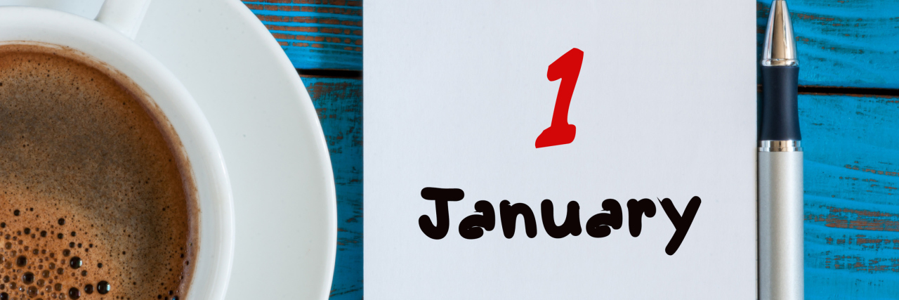 notebook that says january 1st next to mug of hot chocolate