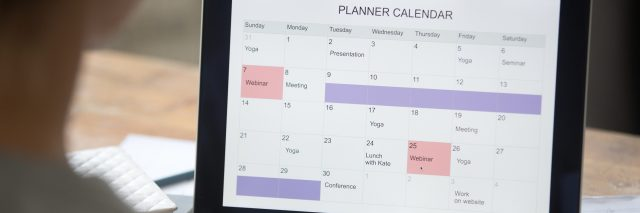 Open laptop on the desk with a planner calendar on the screen.
