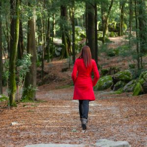 woman in a red coat walking through the forest